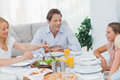 Family around the dinner table smiling Stock Photography