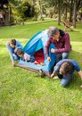 Family assembling tent at campsite of four Stock Images