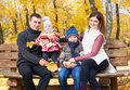 Family in autumn city park sit on bench, parent and children Royalty Free Stock Photo