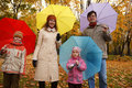Family in autumn park with coloured umbrellas Royalty Free Stock Photo