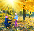 Family in autumn sunshine maple park happy mother with daughter walking golden sunshiny Stock Images