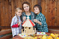 Family in autumn time preparing a bird house woman with two kids for the winter Royalty Free Stock Image