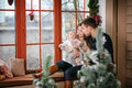 Family with baby boy sitting near the window at home decorated for Christmas Royalty Free Stock Photo