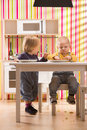 Family baby brother and sister play eat meal in toy kitchen Royalty Free Stock Photo