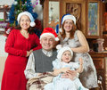 Family with baby girl in santa hats portrait of happy near christmas tree at home Stock Image