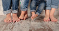 Family barefoot dad mom and daughters in jeans Stock Photography
