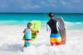 Family beach fun father and son running towards ocean with boogie boards Royalty Free Stock Images