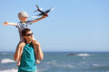 Family at the beach happy adorable boy holding toy plane and sitting on his young handsome father shoulders and having fun Stock Photography