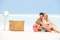 Family on beach with luxury champagne picnic building sand castles Stock Photography