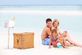 Family on beach with luxury champagne picnic smiling Stock Photo