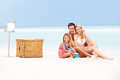 Family on beach with luxury champagne picnic smiling Royalty Free Stock Photo