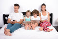 Family in bed modern technology home young the use of tablets and phones lying at home Stock Images