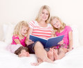 Family on bed reading book Stock Photography