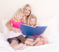Family on bed reading book Royalty Free Stock Photography
