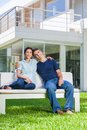 Family in big house couple sitting front of modern embracing sitting bench outdoor dream home Stock Photography