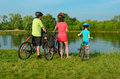 Family on bikes outdoors, active parents and kid cycling and relaxing near beautiful river, fitness Royalty Free Stock Photo