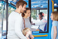 Family boarding bus and buying ticket from driver whilst smiling at each other Royalty Free Stock Photos