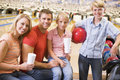 Family in bowling alley with drinks smiling Stock Photography