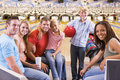 Family in bowling alley with two friends smiling Stock Images
