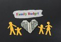 Family budget paper cutout of four with dollar heart and text Stock Photos