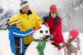 Family Building Snowman On Ski Holiday Royalty Free Stock Images
