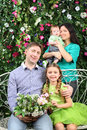 Family with bunch of flowers in garden four near verdant hedge Royalty Free Stock Photos