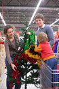 Family buys Christmas-tree with decorations Stock Photo