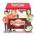 Family buys popcorn from a cute girl seller Royalty Free Stock Photo