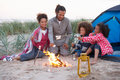 Family camping on beach and toasting marshmallows sitting by camp fire Royalty Free Stock Photography