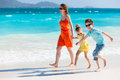 Family at caribbean beach mother and kids on a vacation walking along a Royalty Free Stock Photo