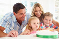 Family celebrating daughters birthday with cake blowing out candles Royalty Free Stock Photos