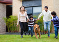 Family chasing a dog Royalty Free Stock Images