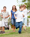Family chasing young kid in the park Royalty Free Stock Images
