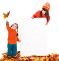 Family with child on autumn leaves holding banner. Royalty Free Stock Image