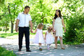 Family with child and pregnant woman walk in summer city park Royalty Free Stock Photo