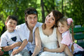 Family and  children on bench in park. Royalty Free Stock Photo