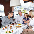 Family with children happy two and grandparents eating in a restaurant Stock Photos