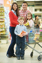 Family with children shopping fruits woman men and child chopping cart during at vegetable supermarket Royalty Free Stock Images