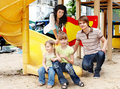 Family with children on slide outdoor. Royalty Free Stock Images
