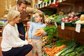 Family choosing fresh vegetables in farm shop young Stock Image