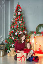 Family on Christmas eve at fireplace. Kids opening Xmas presents. Children under Christmas tree with gift boxes. Decorated living Royalty Free Stock Photo