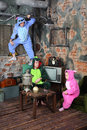 Family in colorful carnival costumes in very old room with television and table with samovar Stock Photos