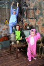 Family in colorful costumes of dragons pose in very old room with table and samovar Stock Photos