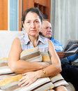 Family conflict portrait of sad women against elderly men with newspaper at home Stock Photos