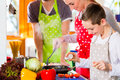 Family cooking healthy food in domestic kitchen with parents and children preparing meal having fun Stock Photography