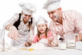 Family cooking together happy in the kitchen while little girl adding eggs in the flour Stock Photography