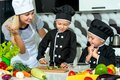 A family of cooks.Healthy eating. Happy family mother and children prepares vegetable salad in kitchen Royalty Free Stock Photo