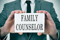 Family counselor a man wearing a suit sitting in a desk with a desktop nameplate in front of him with the word Stock Photography