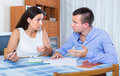 Family couple making shopping list with money problems indoors Stock Photography