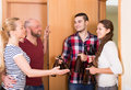 Family couple welcoming visitors at home russian with beer bottles Royalty Free Stock Photography